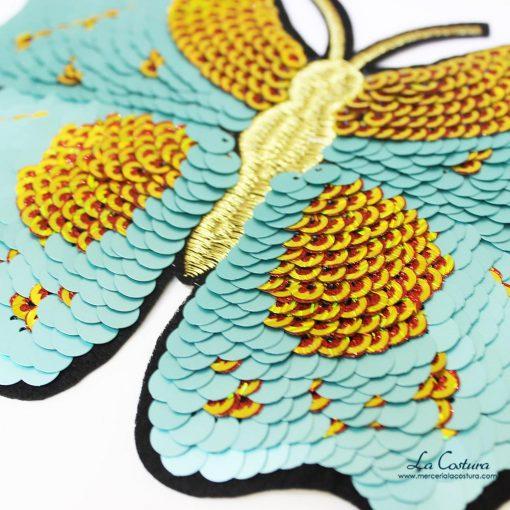 Detalle parche de lentejuelas en forma de mariposa verde agua