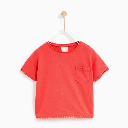 Camiseta niña con madroños en bolsillo, mangas y bajo
