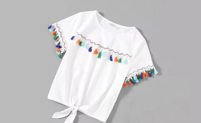 Camisa blanca con flecos y madroños en la espalda. Además