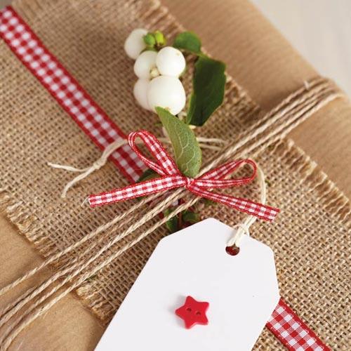 Envoltorio para regalo con cinta de rafia y lazo de cuadros vichy