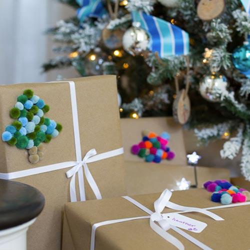 Envoltorio para regalo con pompones de colores y lazo de raso